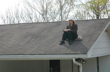 Rachel Held Evans, sitting on the roof while failing to make her book's point.