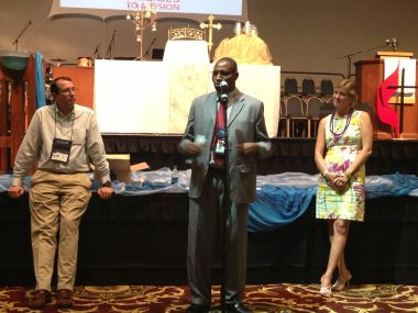 Kenyan UMC pastor Paul Matheri speaks at the North Georgia Annual Conference in Athens, flanked by Bill and Chat Coble.